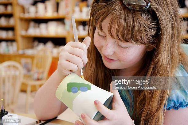 Young redheaded girl painting pottery