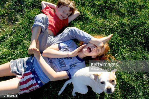 young redheaded girl short hair brown hair laying on her back on grass wrestling younger brother outside on sunny day feet up brother shoving his foot in sisters foot both smiling