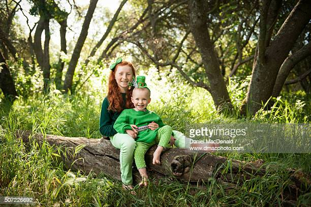 Young redheaded girl sits with toddler sister on a log in a sunny forest dressed festively for Saint Patrick's Day