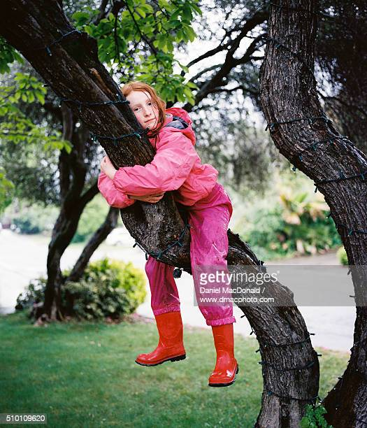 Young redheaded girl sitting in a tree in the rain in rain suit