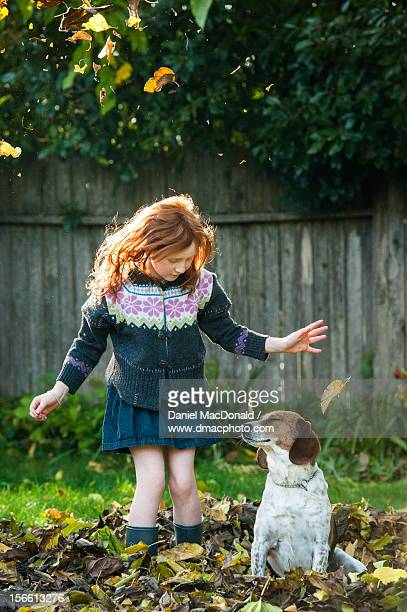 Young redheaded girl with dog in fall leaves