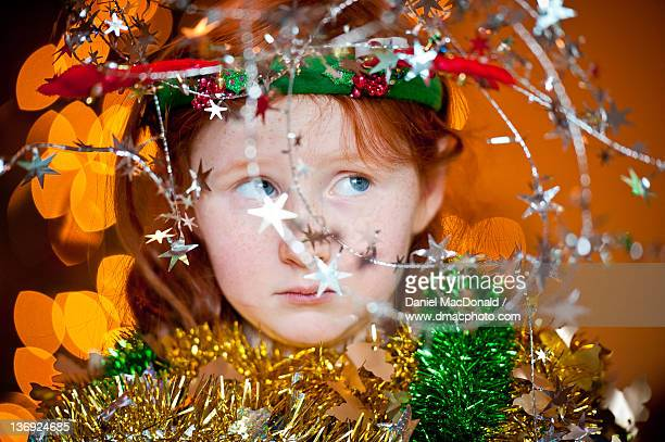 Young redheaded girl wrapped in Christmas ribbons