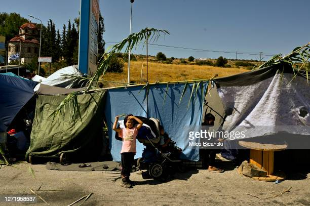 Young refugee child stands in front of an improvised shelter on the side of a road close to Mytilene town after a fire destroyed the Moria refugee...