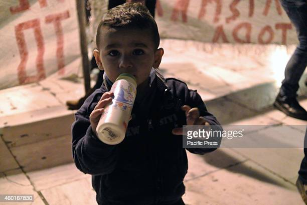 A young refugee drinks milk from a bottleSyrian refugees remain in Syntagma for 20 days in a row now despite of the cold and the rain demanding from...