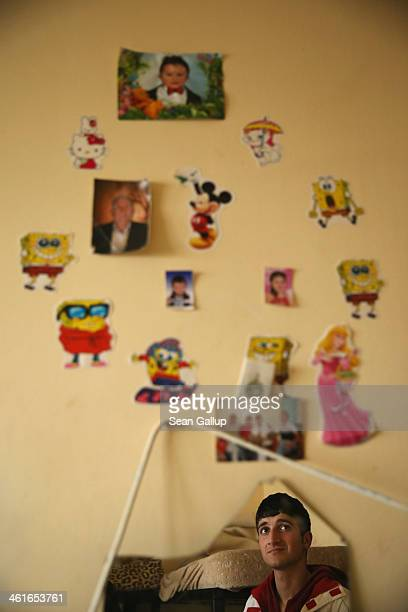 A young refugee from Syria is framed in a broken mirror in the small room that he shares with nine other family members and aquaintances at the main...