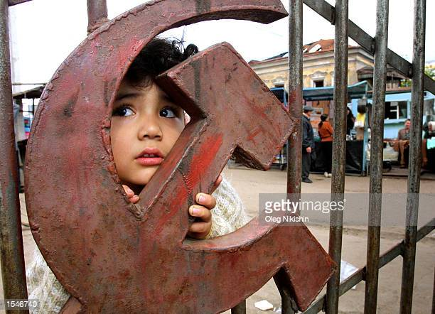 Young refugee girl from Tatjikistan stands near the gate of a food market decorated with a sickle and molot, a symbol of the former Soviet Union May...