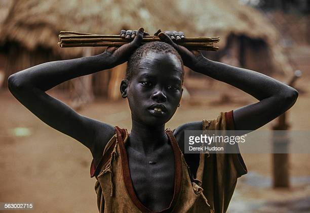 A young refugee plays with firewood at an abandoned mission near Palotaka South Sudan Two hundred kilometres west of the border with Kenya 3000...