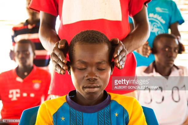 """Young refugees from Sudan practice an activity on """"trauma healing"""" at Doro refugee camp, in Maban, South Sudan, on May 3, 2017. The NGO Jesuit..."""