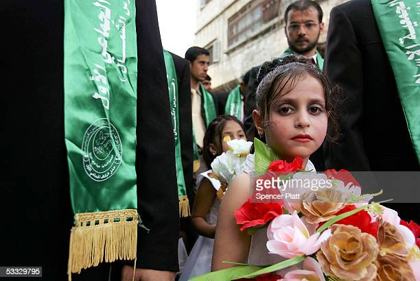 A young relative stands with a groom during a mass wedding organized by the Palestinian party Hamas August 5 2005 in Gaza City the Gaza Strip The...