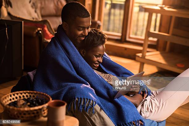 Young relaxed African American couple using digital tablet at home.