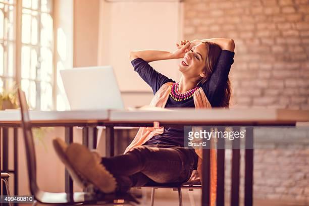 Junge entspannte Geschäftsfrau nimmt eine Pause im Büro.