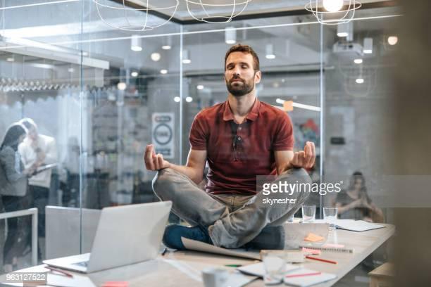 jovem relaxado masculino empresário exercício yoga em cima da mesa no escritório. - budismo - fotografias e filmes do acervo