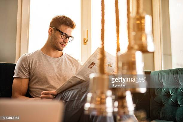 Young relaxed man reading newspaper at home.