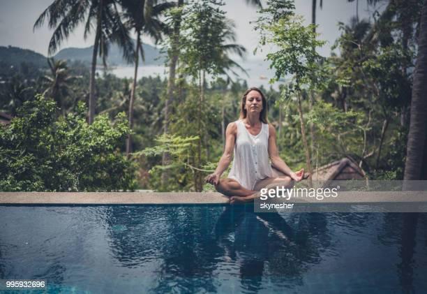young ontspannen vrouw uitoefening van yoga aan de rand van een landschapszwembad. - lotuspositie stockfoto's en -beelden
