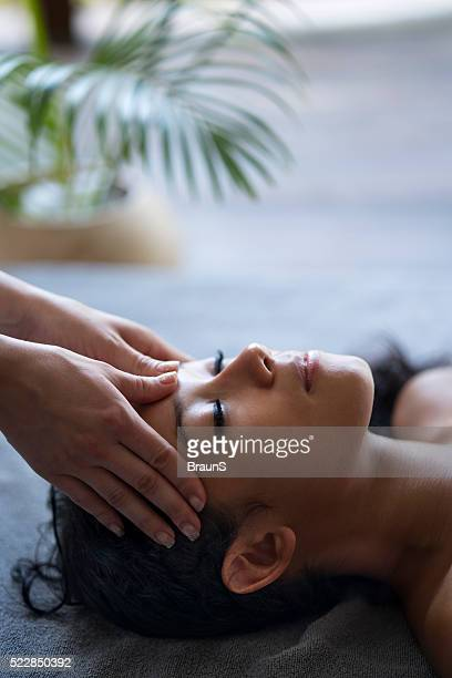 young relaxed woman having a facial massage at the spa. - head massage stock photos and pictures