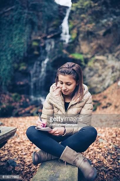 Young Relaxed Woman how Writing by the Waterfall in Autumn