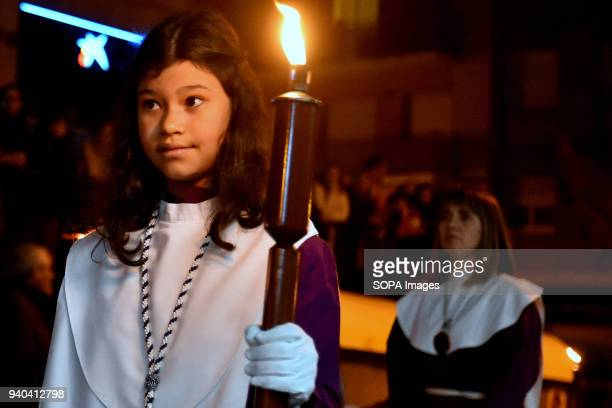 Young religious member seen during the event Penitents who celebrate Easter with the procession of the Holy Burial of Jesus of Nazareth in the city...