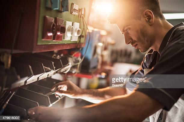 Jungen Handwerker Sie die richtigen Hilfsmittel in einem workshop.