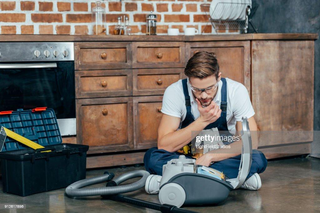 junge Mechaniker in Schutzbrille betrachten defekten Staubsauger : Stock-Foto