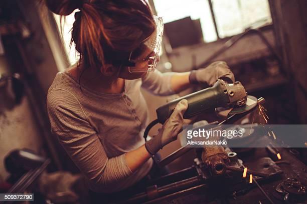 Jeune repairwoman utilisant un Meuleuse