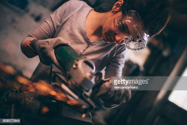 Young repairwoman using a grinder