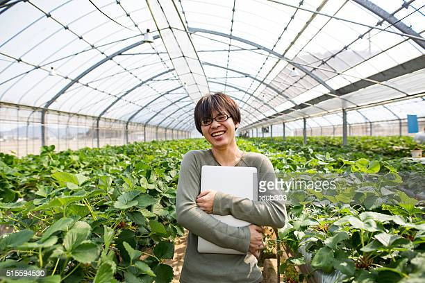 Young researcher with computer in a greenhouse