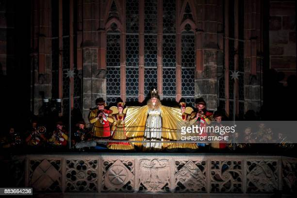 Young resident Rebecca Ammon dressed as the Nuremberg Christkind stands at the balcony of the Frauenkirche Church during the opening of the...