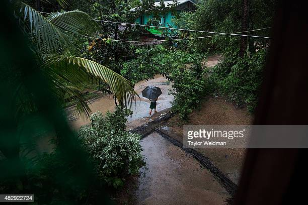 A young resident walks through torrential rain in a village near the planned Dawei SEZ on August 4 2015 in Pantininn Myanmar The controversial...
