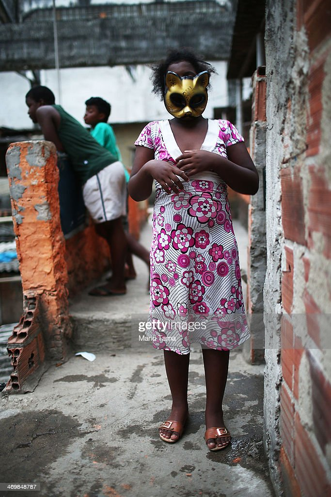 A young resident wears a Carnival mask inside a formerly deserted bullding which is currently occupied by 82 families in the port district on February 16, 2014 in Rio de Janeiro, Brazil. Residents say the building has been occupied for the past 14 years and government officials have informed the residents that they will be relocated to new housing in the North Zone of the city ahead of the 2014 World Cup. Some residents doubt the intentions of the government. Ahead of the 2014 World Cup and Rio 2016 Olympic Games, Rio has started a multibillion dollar urban renewal program of its port district which includes a double decker waterfront freeway torn down to be replaced by tunnels, repaved roads, a tram network and other infrastructure improvements in the area. The 'Porto Maravilha' project is also expected to displace around 1,000 local residents.