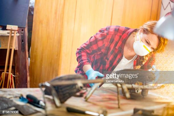 Young Restorer Woman Wearing a Protection Mask while Spraying Antiques