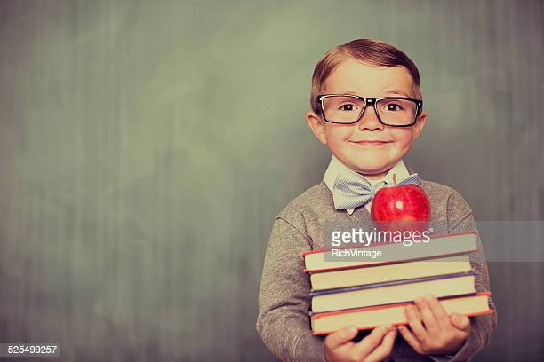 Young Retro Boy Holding Books in Classroom