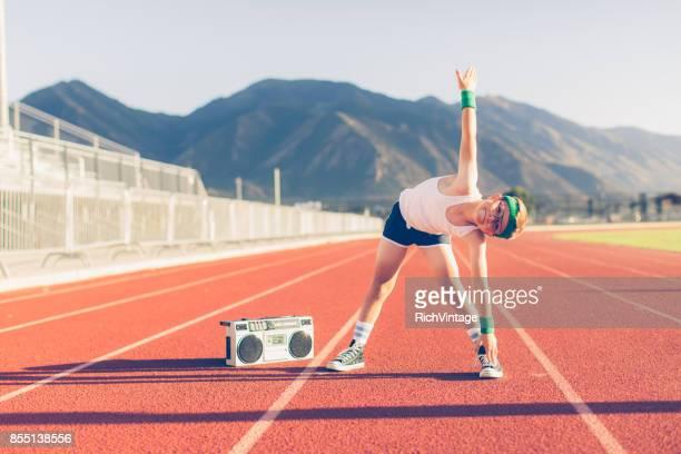 Joven Retro Fitness Boy escuchando música mientras estirar