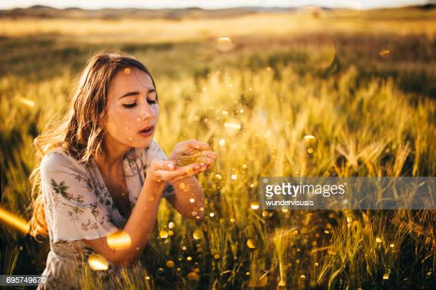 Young retro girl blowing golden glitter in a wheat field