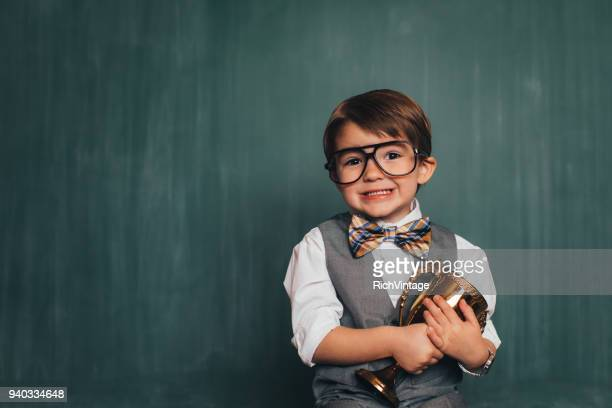 young retro nerd boy in classroom with trophy - award stock pictures, royalty-free photos & images