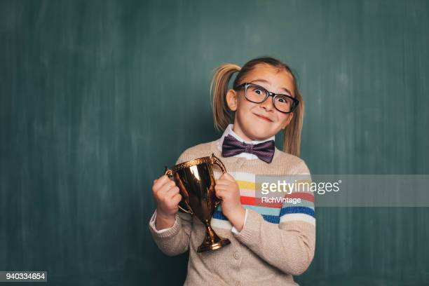 young retro nerd girl in classroom with trophy - geek girl stock photos and pictures