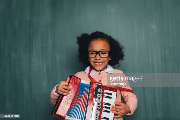 young retro nerd girl playing accordion - accordion instrument stock pictures, royalty-free photos & images