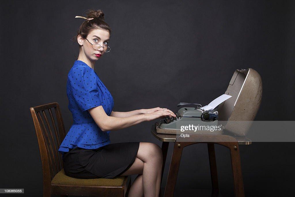 Young retro secretary typing : Stock Photo