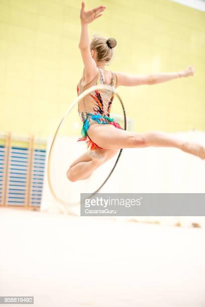 Gymnastique rythmique jeune athlète attraper le cerceau en milieu aérien