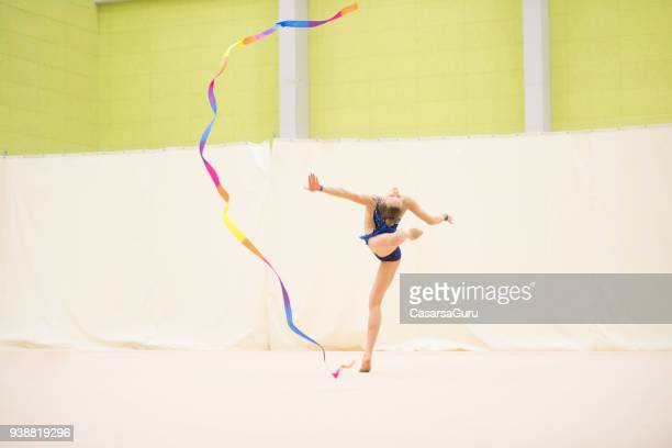 young rhythmic gymnastics athlete dancing with ribbon - rhythmic gymnastics stock pictures, royalty-free photos & images
