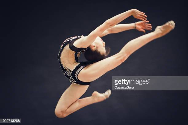 Young Rhythmic Gymnastics Athlete Doing a Pose in Mid Air