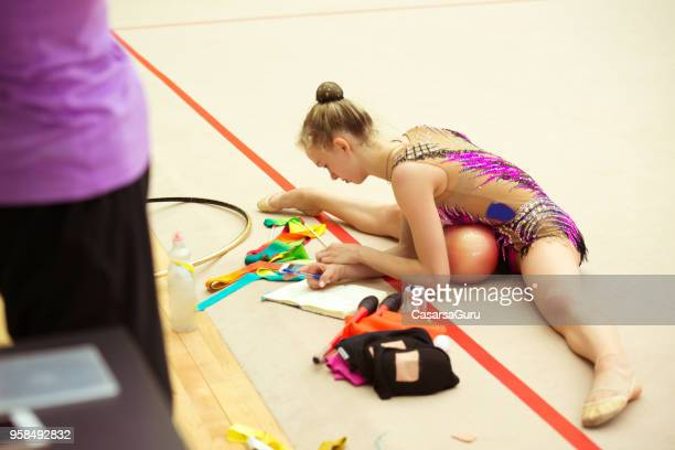 Young Rhythmic Gymnastics Athlete Taking Notes During Training