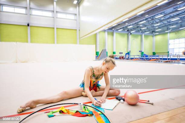 young rhythmic gymnastics athlete taking notes on training - daily sport girls stock pictures, royalty-free photos & images