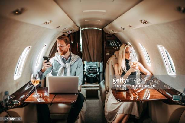 young rich and successful couple looking away from each other while travelling in a private airplane - divorce stock pictures, royalty-free photos & images