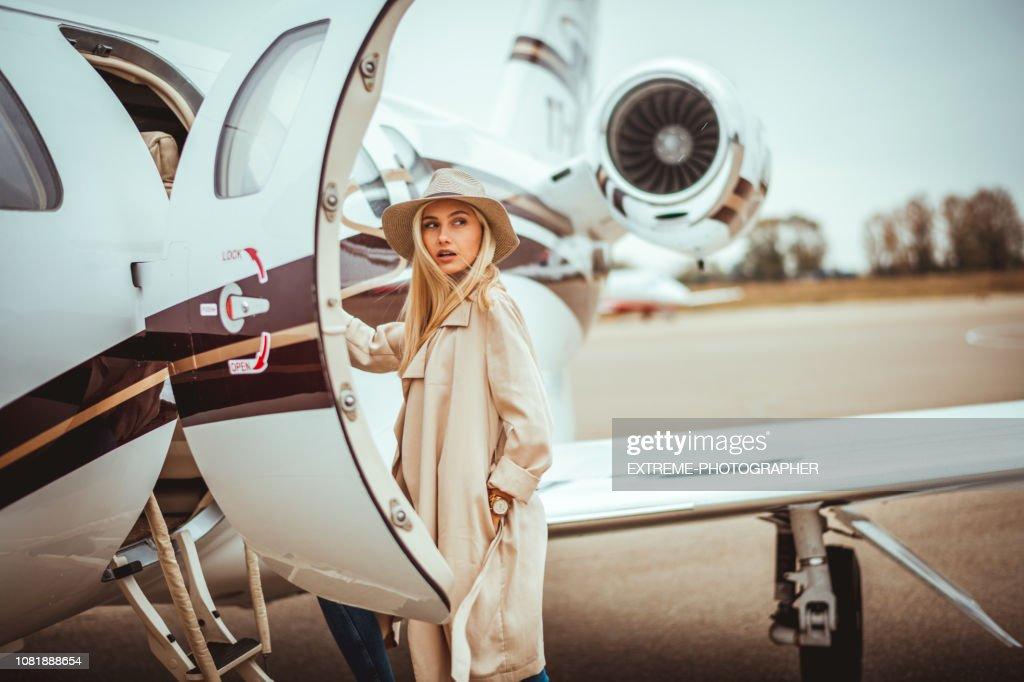 Joven rica rubia mujer mirando sobre su hombro al entrar en un avión privado estacionado en una pista de aeropuerto : Foto de stock