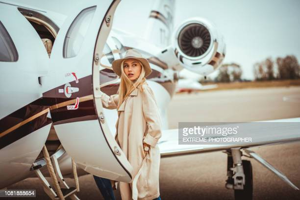 young rich blonde female looking over her shoulder while entering a private airplane parked on an airport tarmac - ricchezza foto e immagini stock
