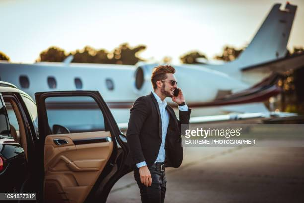 young rich businessman talking on a mobile phone while getting out of a luxurious car parked next to a private airplane on a tarmac - high society stock pictures, royalty-free photos & images