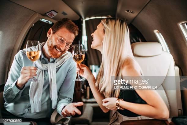 jovem casal rico desfrutando vinho e fazer um brinde ao sentar ao lado do outro em um avião privado - bêbado - fotografias e filmes do acervo
