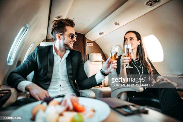 young rich couple making a toast during a meal while sitting next to each other on a private airplane - stereotypically upper class stock pictures, royalty-free photos & images