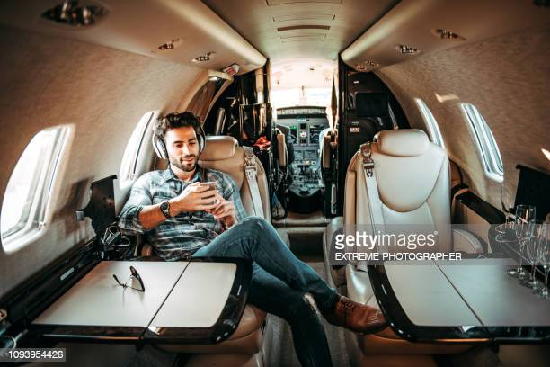 young rich man listening to music over the headphones and using a mobile phone while sitting in a private jet - vip stock pictures, royalty-free photos & images