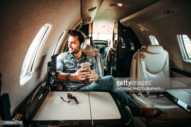 young rich man looking out of the window while listening to music over the headphones and using a smart phone, sitting in a private jet - millionnaire stock pictures, royalty-free photos & images